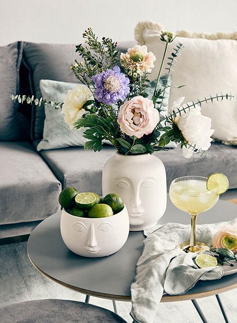 żółty drink z cytryną na stoliku kawowym obok białego wazonu z kwiatami