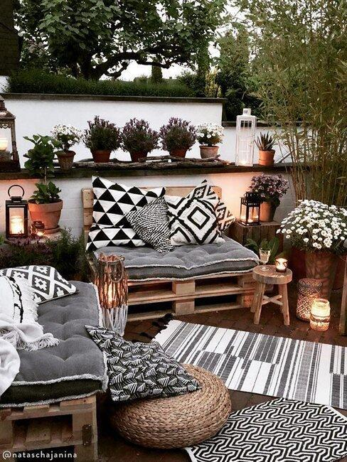 Ławki z palet z poduszkami i dywanikiem w kolorach szarości, bieli i czerni