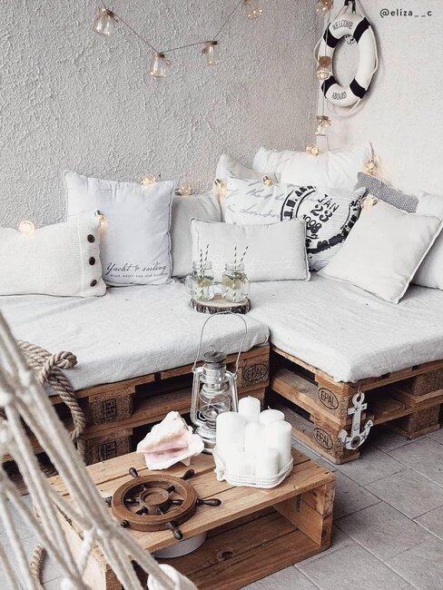 Ławka z palet z białymi poduszkami siedziska
