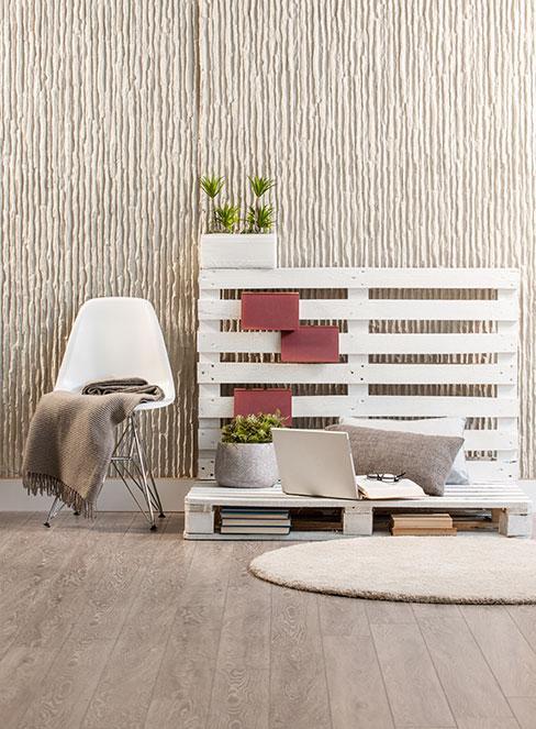 Ławka z palet obok krzesła i dywanu na ziemi