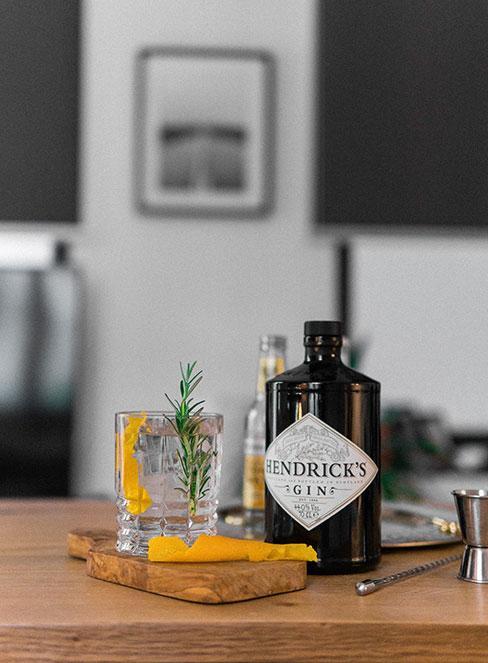 Karafka ginu z tonikiem obok kryształowej szklanki z rozmarynem i pomarańczą