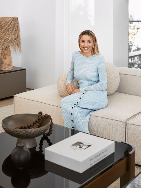 Delia w błękitnej sukience siedząca na beżowej sofie