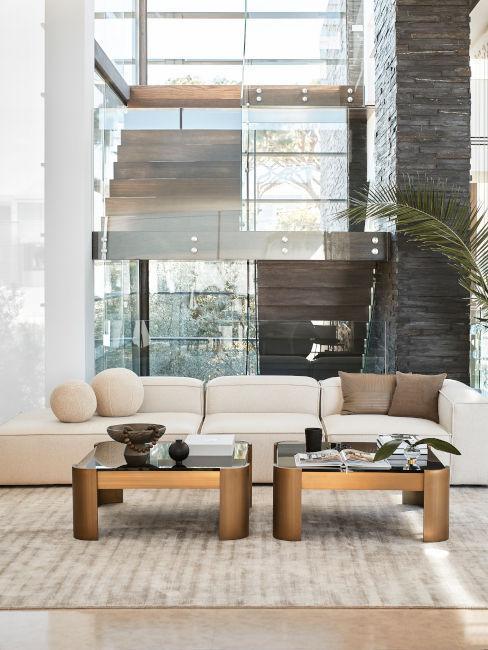 przeszklony loft z szarą sofą modułową i dwoma stolikami kawowymi