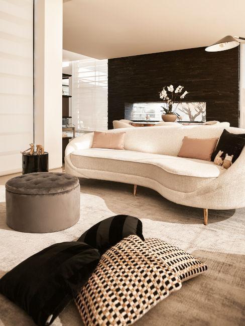 beżowa sofa nerka obok szarej pufy w lofcie