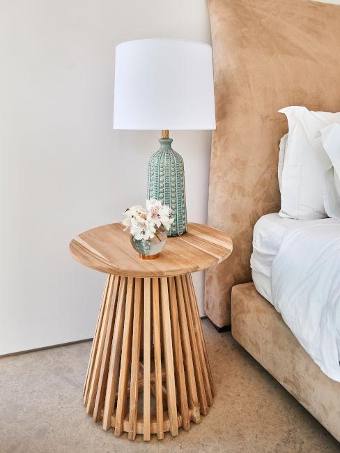 zbliżenie na drewniany stolik obok łóżka z aksmaitu