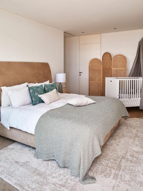 sypialnia w stylu boho z łóżkiem z brązowego aksamitu i parawanem z rattanu