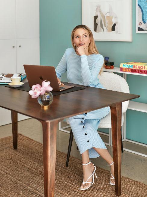 Delia Lachance siedząca za drewnianym biurkiem w biurze z zieloną ścianą