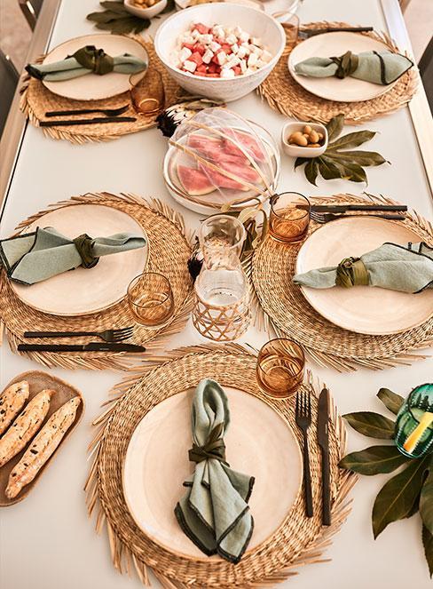Stół nakryty talerzami i dekoracjami w stylu tropikalnym