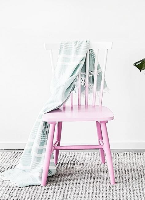 Różowe krzesło z jasną narzutą w jasnym pomieszczeniu