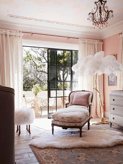 sypialnia w pudrowym różu z antycznym szezlongiem i lampą podłogową z piórami