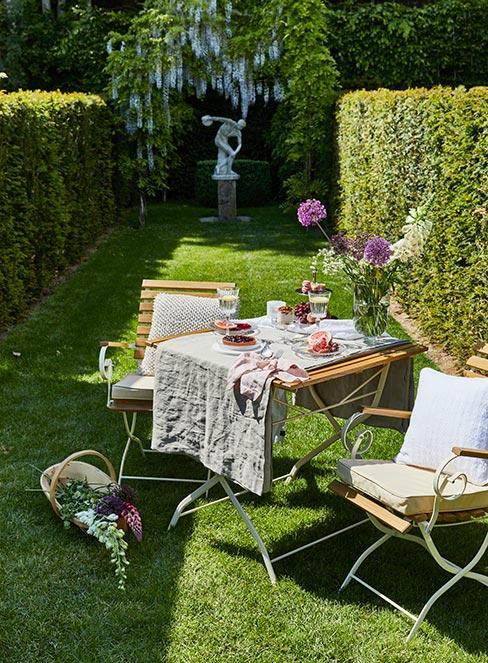 drewniane meble ogrodowe z lnianym obrusem i kwiatami w ogrodzie francuskim