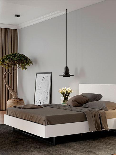 Łóżko z brązową narzutą i drzewem bonsai obok