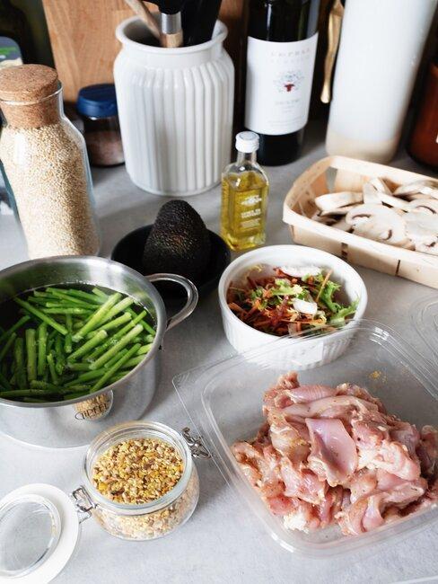 Garnek z fasolką obok mięsa, oliwy i sałatki