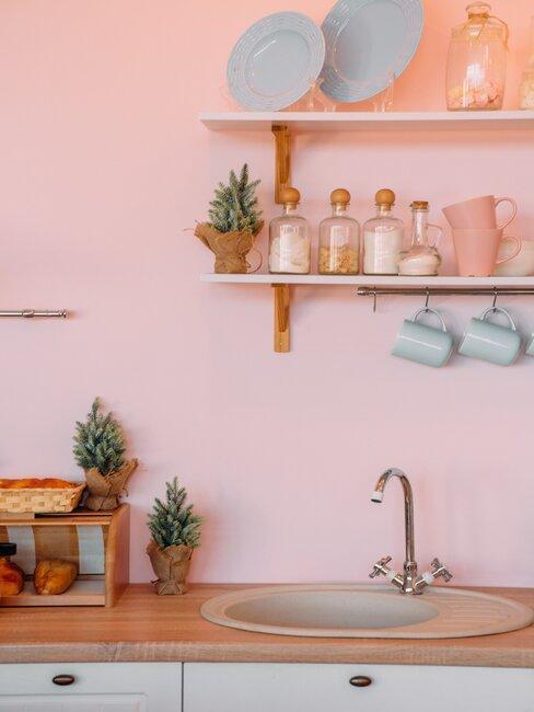kuchnia z różową ścianą z pastelowymi naczyniami