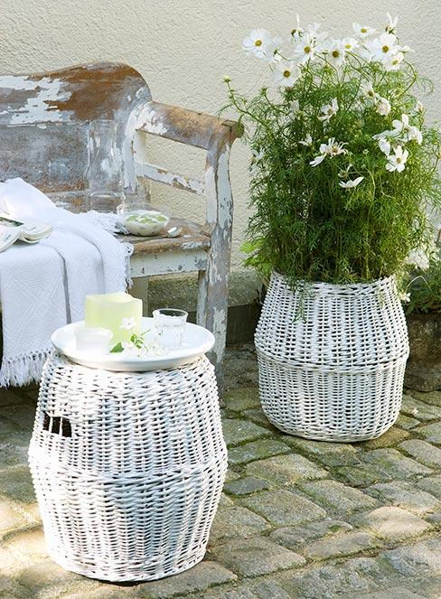 ławka ogrodowa z odchodzącą farbą obok białego kosza z kwiatami