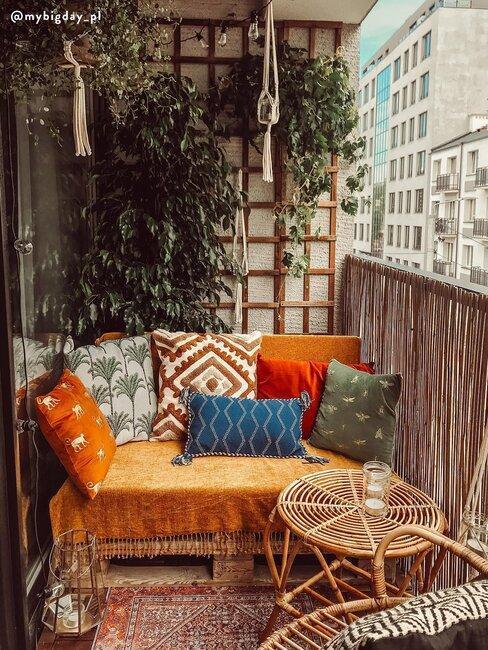 brązowa ławka z apalet z kolorowymi poduszkami na balkonie w stylu boho