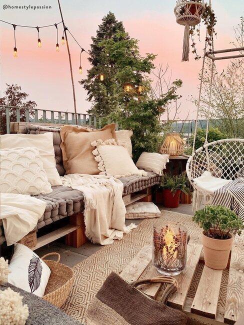 ławka z ciemnych palet na tarasie z jasnymi poduszkami w stylu boho obok fotela wiszącego