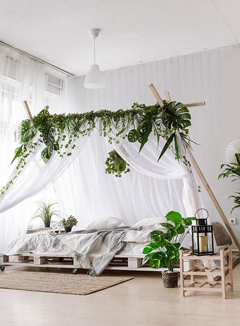 Łóżko z palet w przestronnej sypialni boho z baldachimem i roślinami