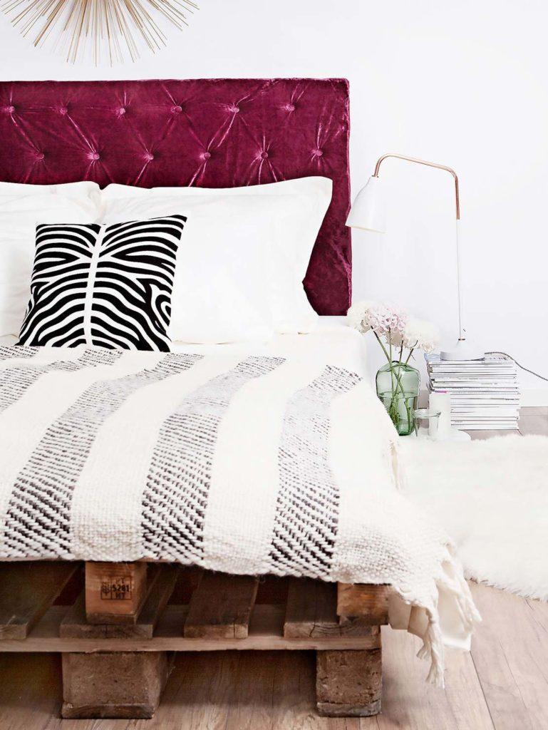 Łóżko z palet z purporowym zagłówkiem z aksamitu