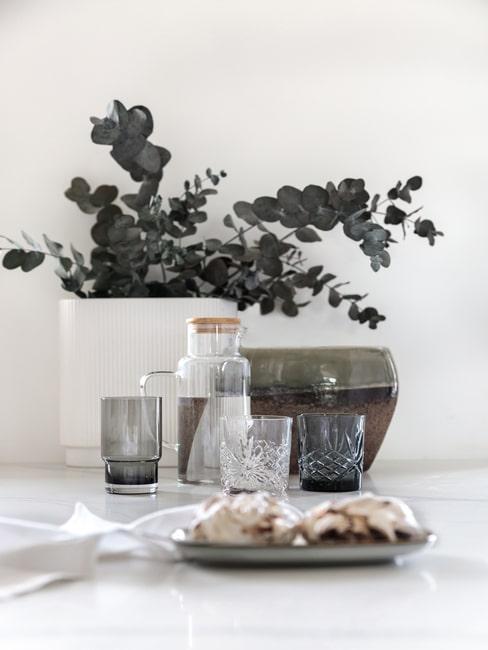 Szklanki na blacie w kuchni oraz wazon z eukaliptusem