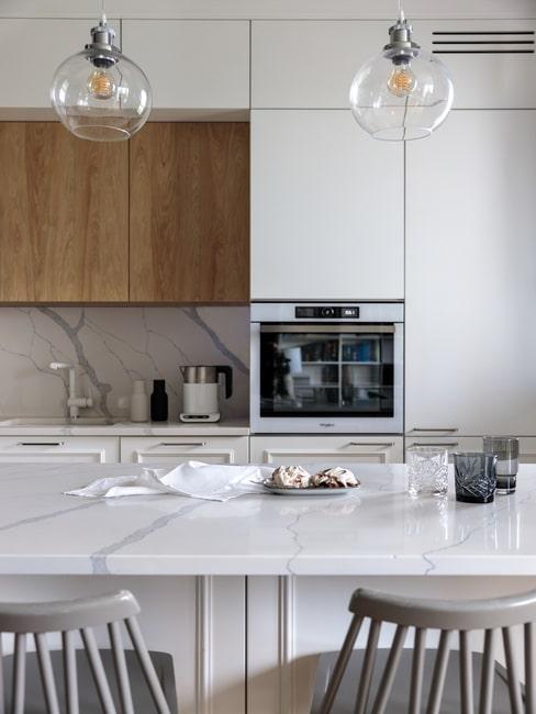 Biała kuchnia z marmurowym blatem i wysokimi drewnianymi krzesłami