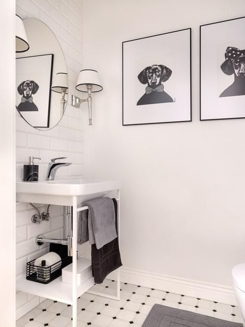 Biała łazienka z grafikami psów na ścianie