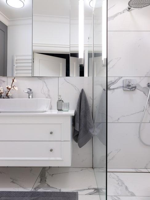 Biała łązienka ze ścianami pokrytymi marmurem