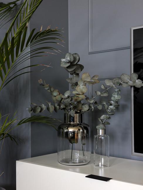 Gałązki eukaliptusa w szklanych wazonach na szafce RTV