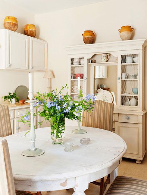 kuchnia w stylu prowansalskim z okrągłym stołem z bielonego drewna i kredensem