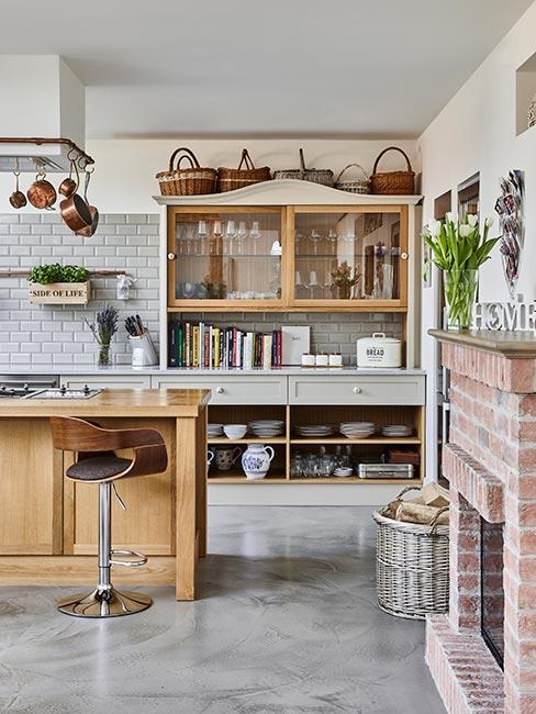 kredens w kuchni rustykalnej z kominkiem z czerwonej cegły