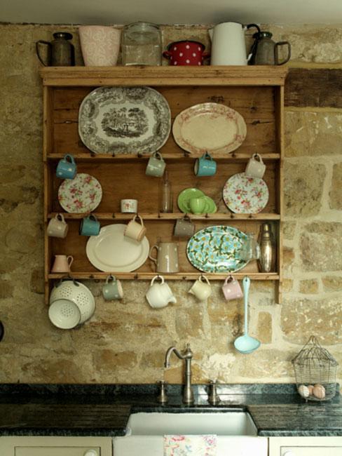rustykalna kuchnia z półką ścienna z naczyniami na tle ściany z kamienia