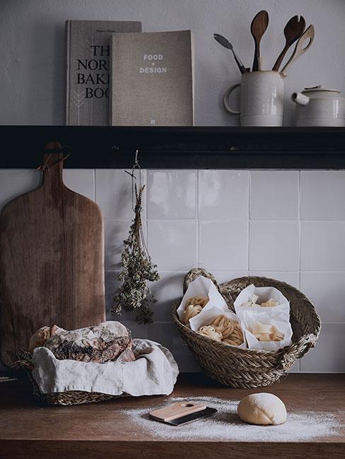 kuchnia z półkami w ciemnym drewnie i drewnianym blatem z deską do krojenia i koszem w stylu rustykalnym