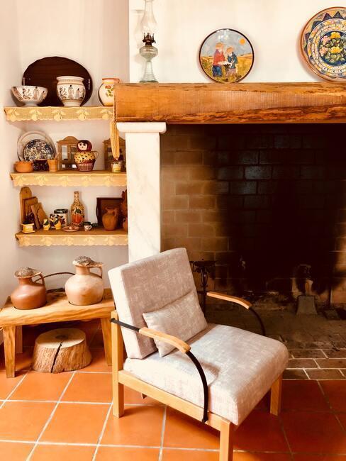 fotel przy kominku obok regału z naczyniami z kamionki w stylu rustykalnym