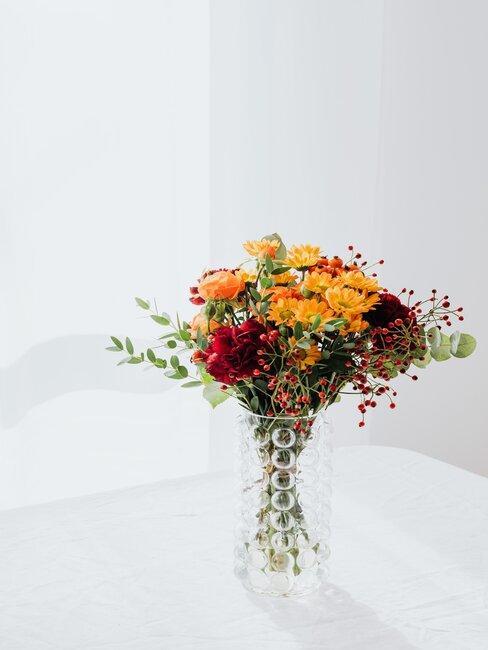 Piękne kolorowe kwiaty ułożone w wysokim przezroczystym wazonie