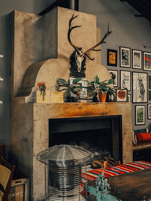 Salon z dużym betonowym kominkiem w stylu industrialnym z porożem