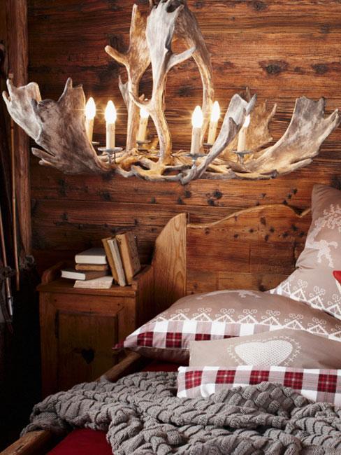 lampa z poroża jelenia w drewnianej sypialni w stylu rustykalnym