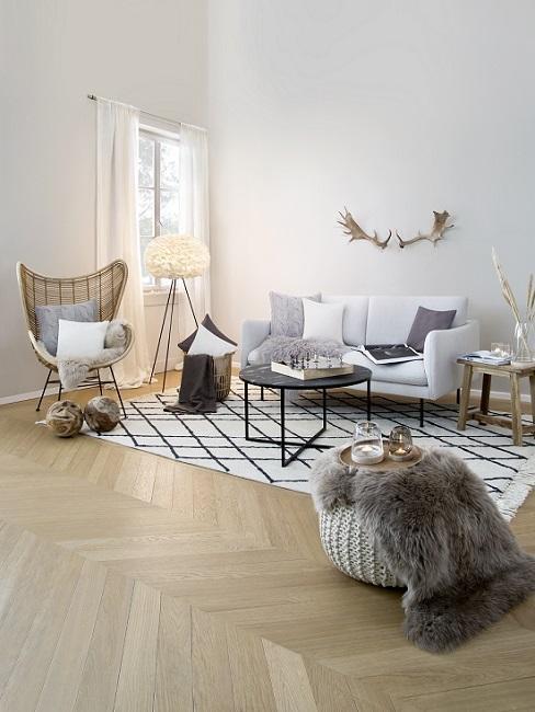 mały szary salon w stylu country z ażurowym fotelem i dekoracjami z futra