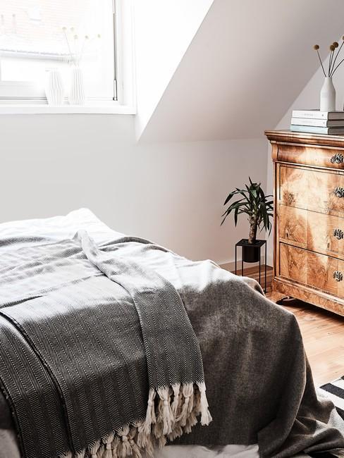 sypialnia w stylu country z drewnianą komodą na poddaszu