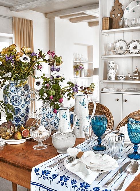 białe naczynia w niebieskie kwiatki na drewnianym stole z kredensem w w sytlu country w tle