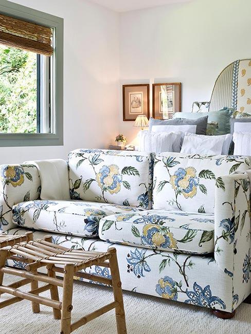 mały salon z sofą w kwiaty przy drewnianych stołkach