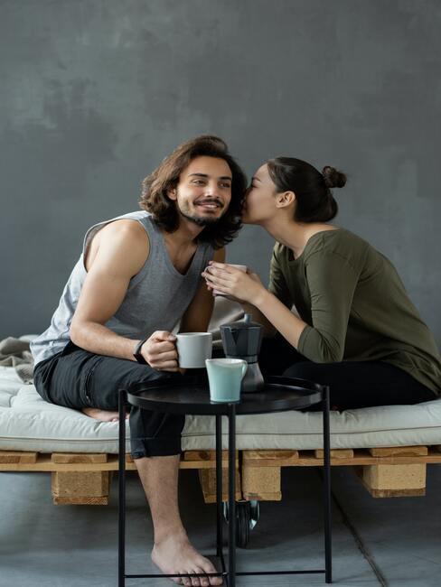 para siedząca na łóżku z palet