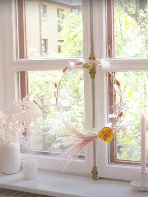 delikatny wianek z suszonej trawy i owoców na oknie w stylu boho