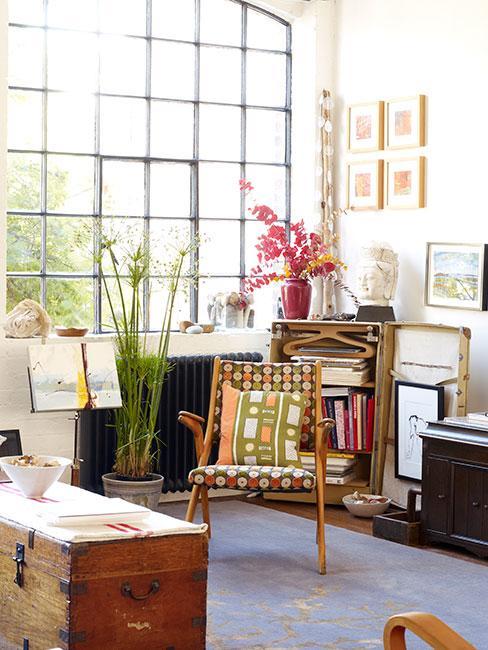 kącik do czytania w lofcie z dużym oknem pofabrycznym z roślinami i dekoracjami vintage