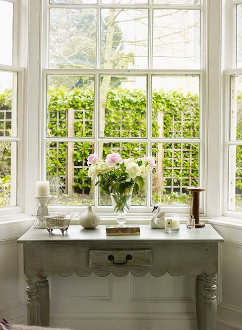 konsola pod oknem w stylu prowansalsskim z dekoracjami i wazonem róż