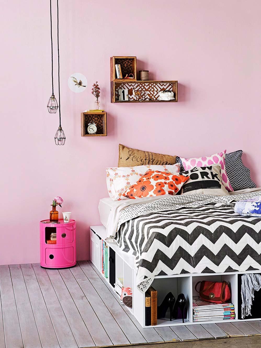 łóżko DIY z szuflad w sypialni z różową ścianą i półkami ze skrzynek na różowej ścianie