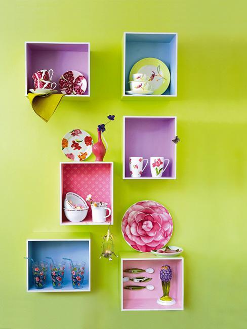 kolorowe półki ze skrzynek na zielonej ścianie