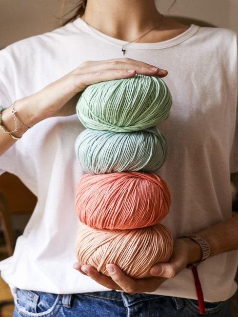 Zbliżenie na 4 motki wełny w pastlowych kolorach trzymanych przez kobietę