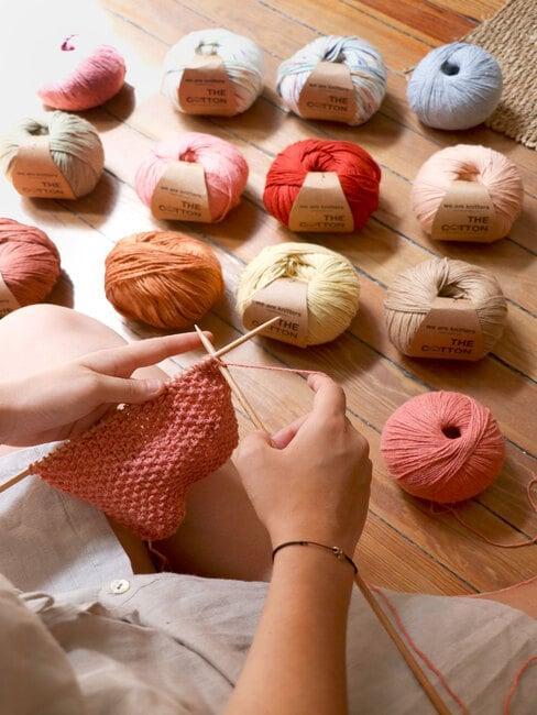 Dłonie osoby robiącej na drutach i motki wełny w wielu kolorach