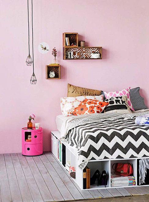 łożko zrobione ze skrzynek z szufladami w sypialni z różową ścianą i industrialną lampą żarówką na kablu