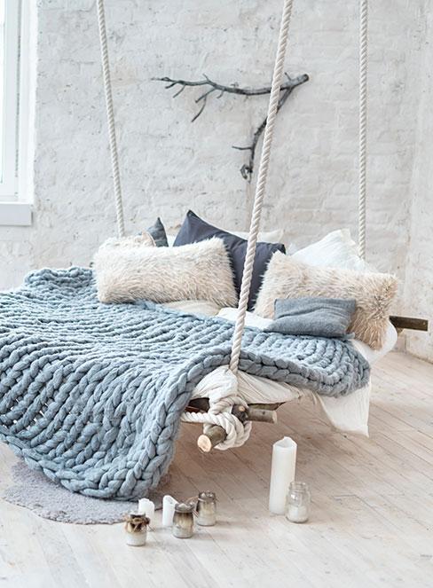 wiszące łóżko na białych linach nakryte grubym błękitnym pledem